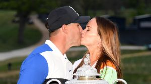 FARMINGDALE, NEW YORK - MAY 19: Brooks Koepka of the United States poses with girlfriend Jena Sims and the Wanamaker Trophy during the Trophy Presentation Ceremony after winning the final round of the 2019 PGA Championship at the Bethpage Black course on May 19, 2019 in Farmingdale, New York.