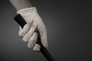 Closeup of a golfers hand on the handle of a golf club.