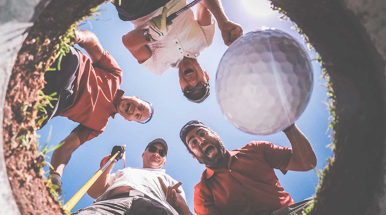 Golf friends look at a ball in a cup.