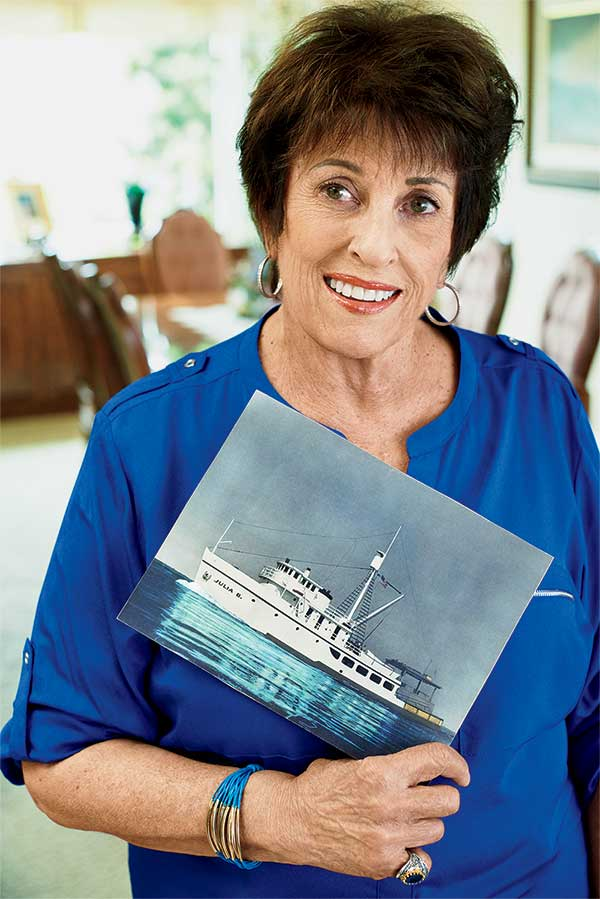 Mary, Phil's mother, holds a photo of the Julia B., Al's fishing boat.