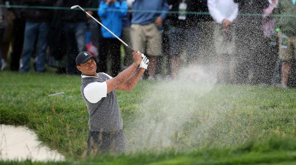 Tiger Woods blasts out of a bunker during the first round of the 2019 U.S. Open.