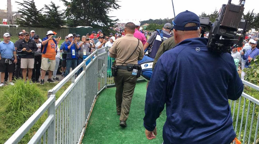 Officer Arroyos walks behind Jason Day and caddie Steve Williams (and in front of a cameraman) on his way to the 17th tee box on Thursday at Pebble Beach.