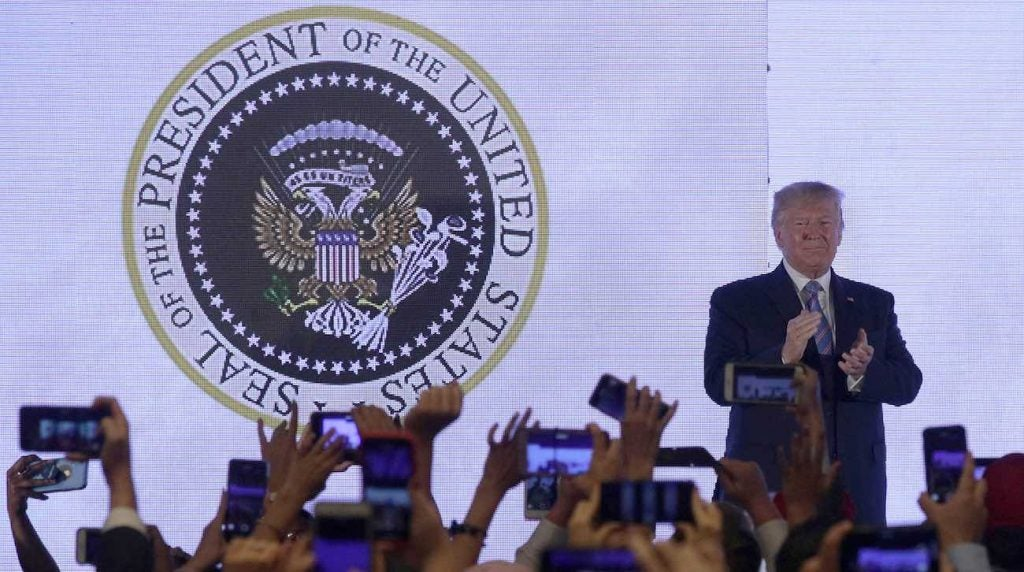 Donald Trump applauds in front of a doctored presidential seal with a double headed eagle and a set of golf clubs.