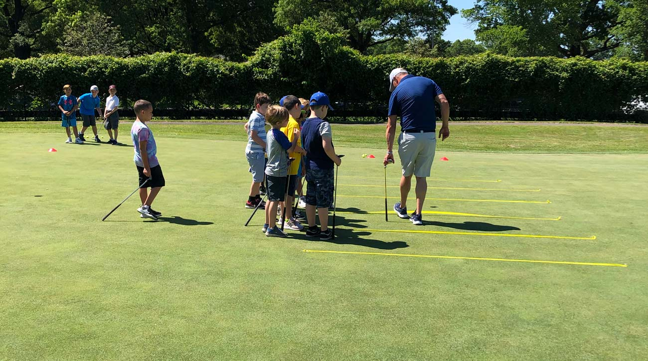 A group of students watch one of the golf instructors explain a putting game at the Brooklyn junior golf center in Dyker Heights.