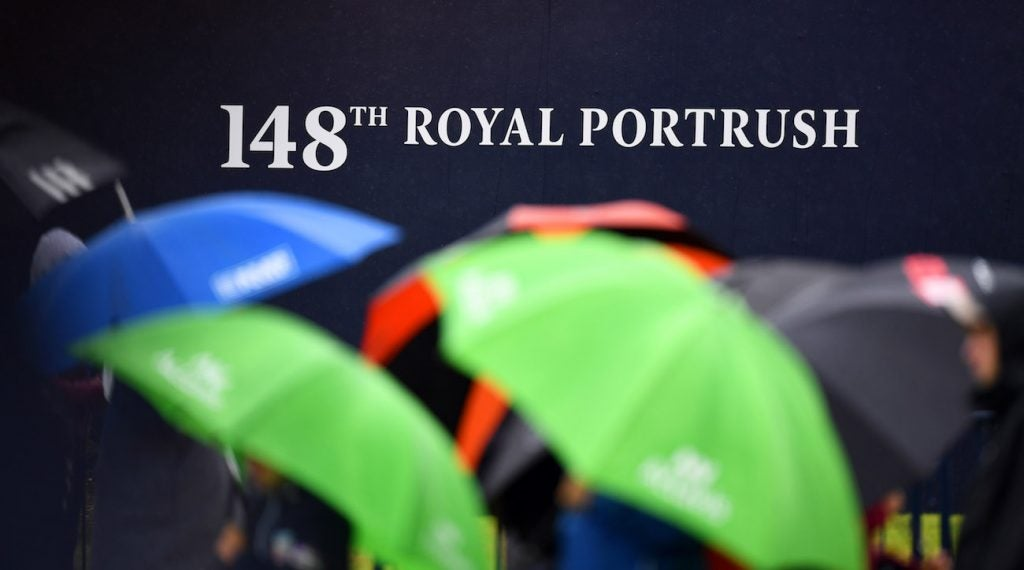 Golf fans converge with umbrellas due to cold, windy and wet weather during a practice round of The Open Championship golf tournament at Royal Portrush Golf Club.