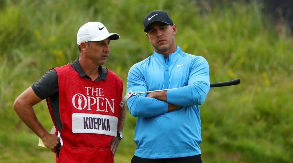 Brooks Koepka and his caddie Ricky Elliott talk over a shot at the Open Championship.