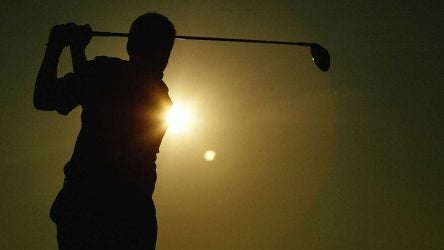 Man hits driver on golf course.