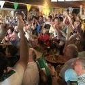 Those packed into the Esker Hills clubhouse cheer as Shane Lowry clinches his Open Championship victory on Sunday.