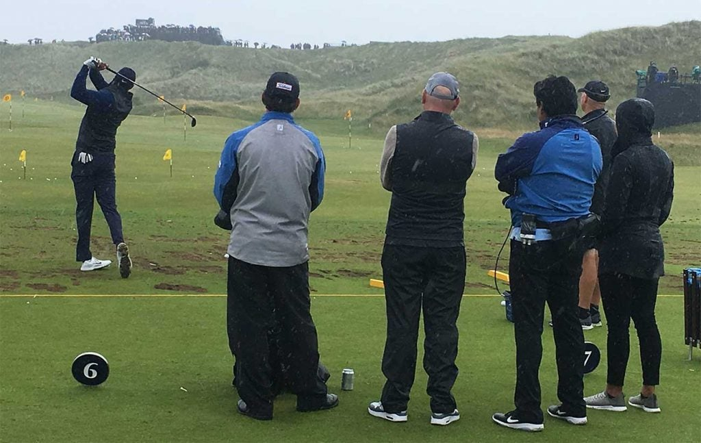 Tiger Woods hits shots on the range as his entourage watches behind him.