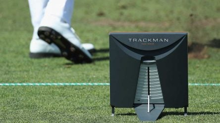 A player hits off the range with his Trackman nearby.