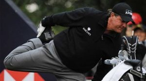 Phil Mickelson stretches his quadriceps before teeing off.