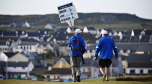 A sign bearer walks down the fairway at a tournament.
