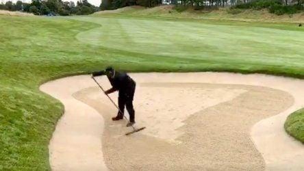 A greenskeeper rakes a bunker.