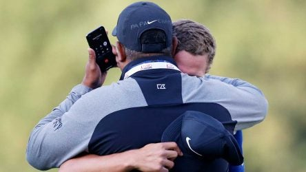 Cameron Champ hugs his dad while his grandfather is on the phone after Champ's Safeway Open title.