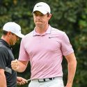 Rory McIlroy fist pumps at the Tour Championship with Brooks Koepka behind him.