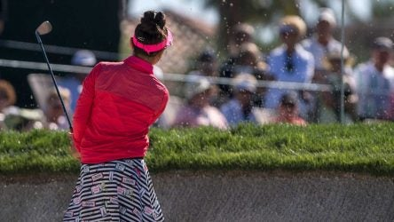 A junior golfer blasts out of the bunker.