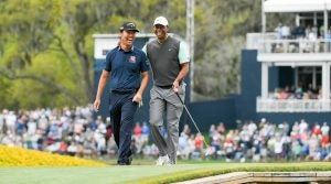 Tiger Woods and Kevin Na walk off the 17th green at TPC Sawgrass during the 2019 Players.