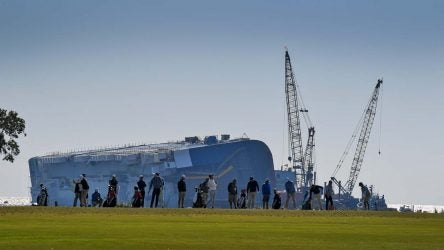 PGA Tour pros warm up on the range Wednesday with the massive capsized Golden Ray cargo ship looming in the background
