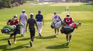 Golfers walk off the tee at a tournament.