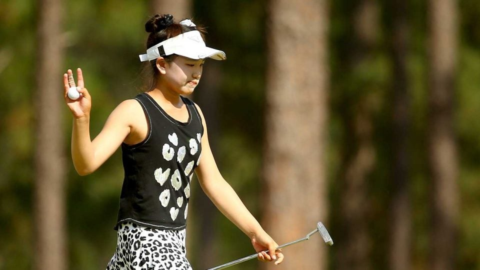 Lucy Li waves to the gallery at the 2014 U.S. Women's Open at Pinehurst, which Li was competing in as an 11 year old.
