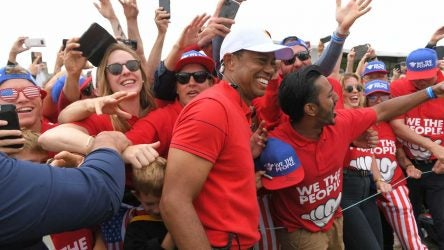 Tiger Woods celebrates with Presidents Cup fans after the Americans' victory in Australia.