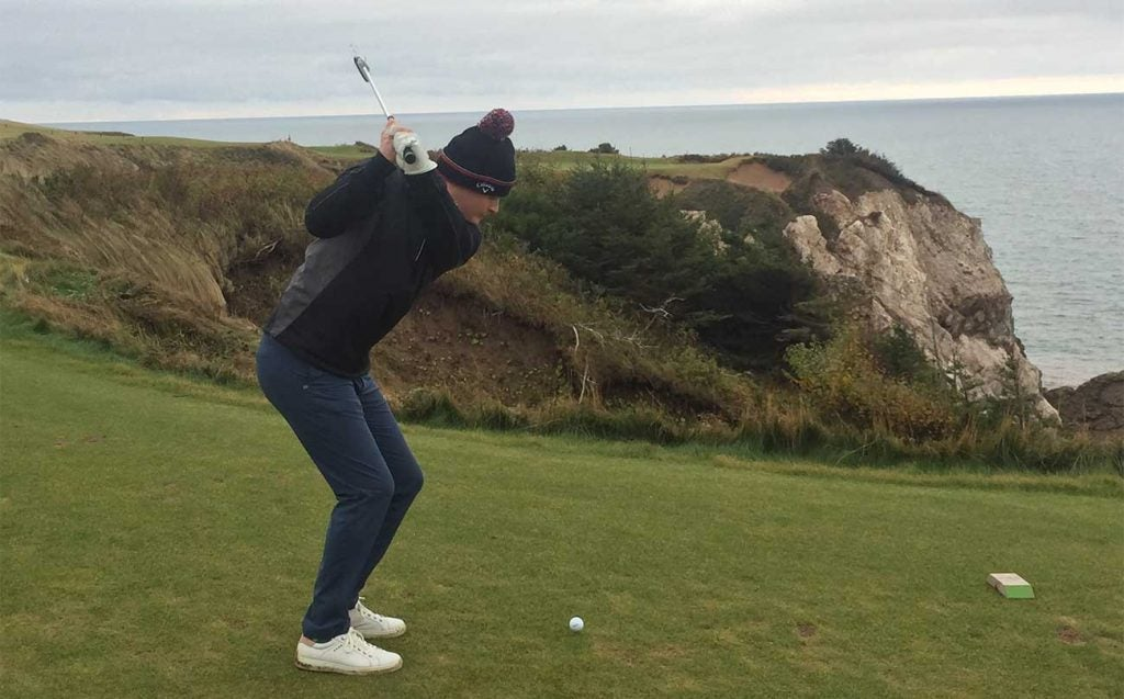 Teeing off on the par-3 16th at Cabot Cliffs.
