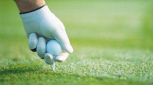 A golfer tees up a golf ball.