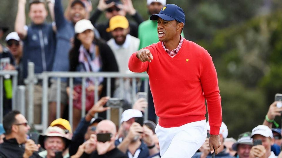 Tiger Woods yells to Justin Thomas to get his golf ball after chipping in at the Presidents cup.