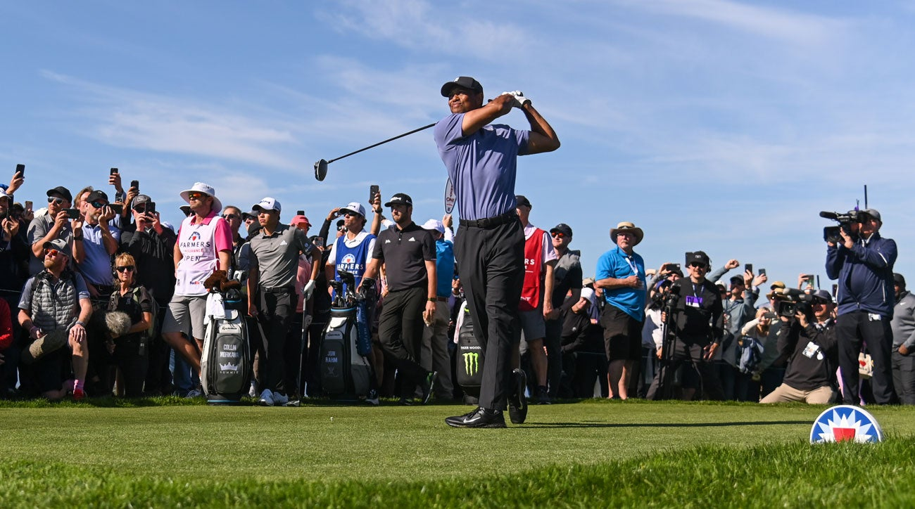Tiger Woods tees off in front of his usually large group of fans.