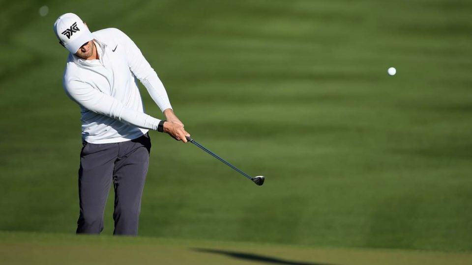 Golfer hitting wedge shot.