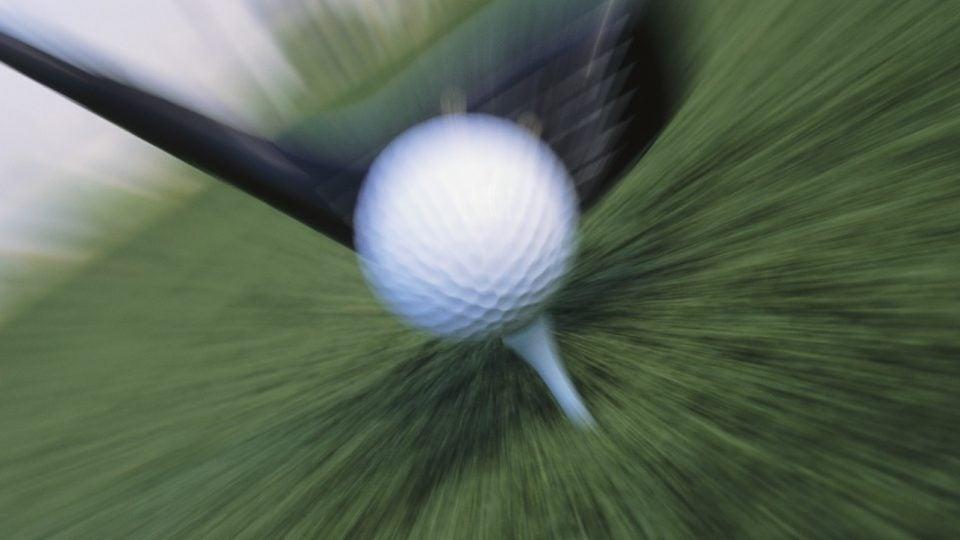 A clubhead hitting a golf ball at high speed