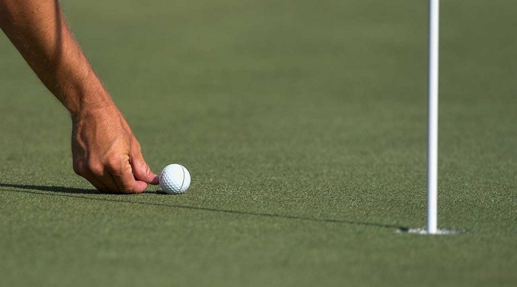 A pro golfer marks their golf ball on the green.