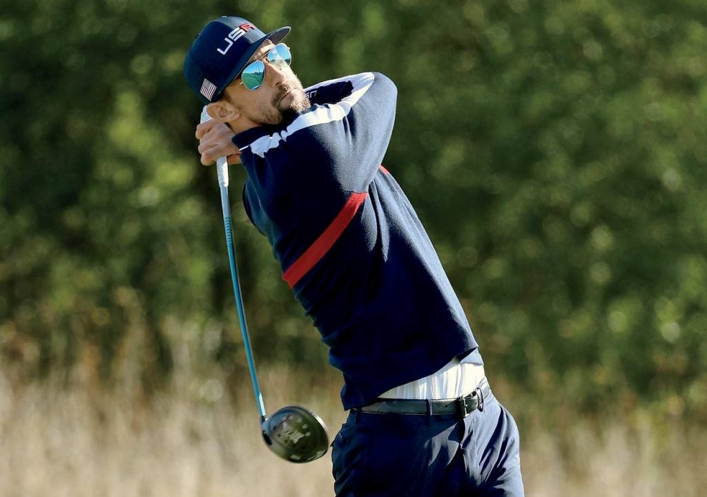 Michael Phelps plays a shot during the celebrity challenge match ahead of the 2018 Ryder Cup.