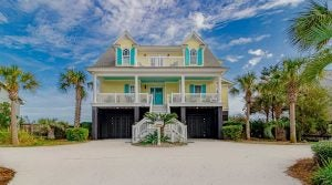 Yellow beach house with blue shutters in Myrtle Beach, South Carolina.