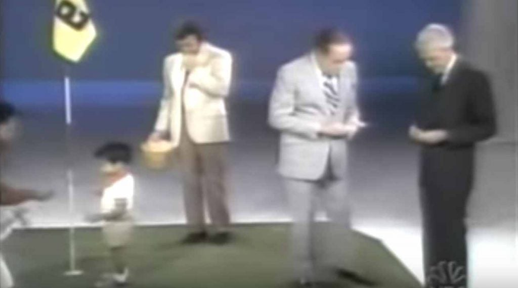Bob Hope pulling out a wad of cash to bet against Woods.