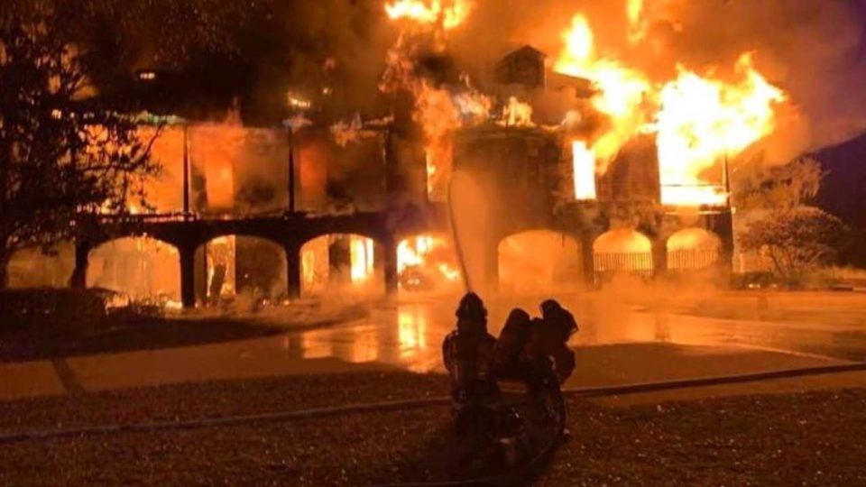 Firefighters try to put out the blaze at the home of Davis Love III on Friday morning.