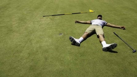 Golfer lying on putting green with his arms and legs open wide feeling exhausted.