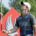 Rory McIlroy balances a golf club.