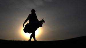 A caddie walks down the fairway holding a golf bag.