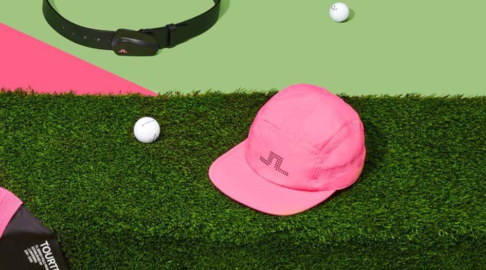 J.Lindeberg pink hat and black leather belt surrounded by golf balls