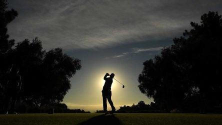 golfer swings sun in background