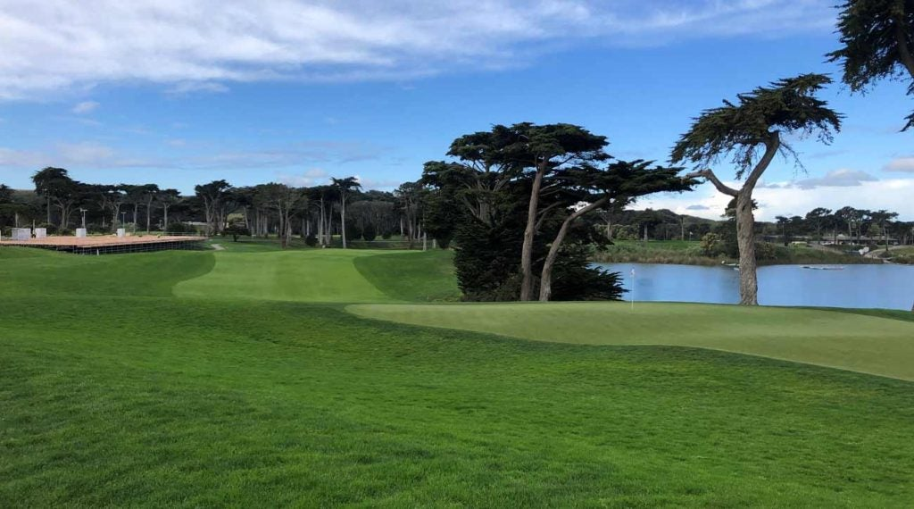 An empty fairway at Harding Park with PGA Championship infrastructure in the background.