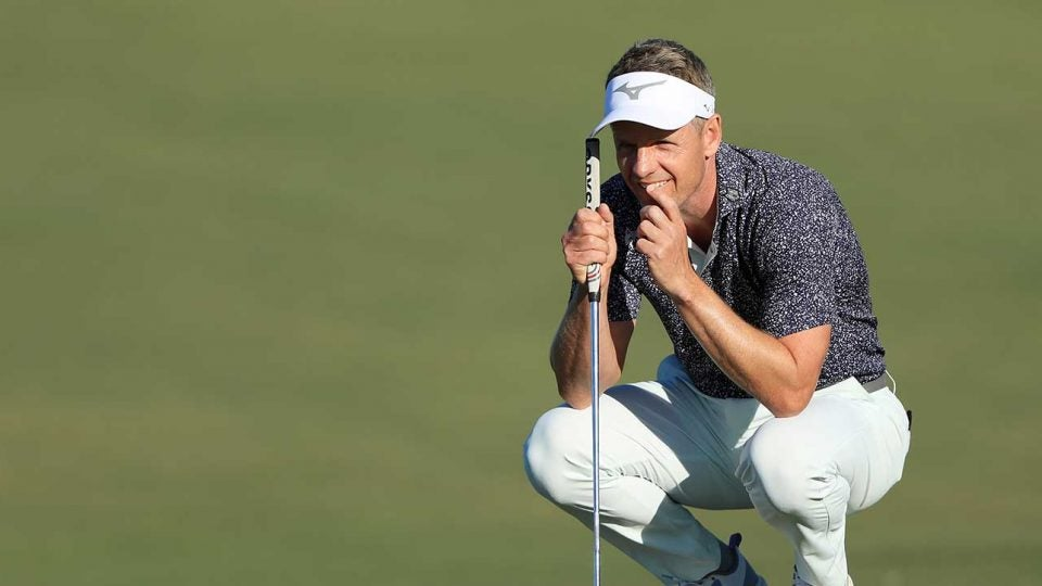 Luke Donald crouches putt