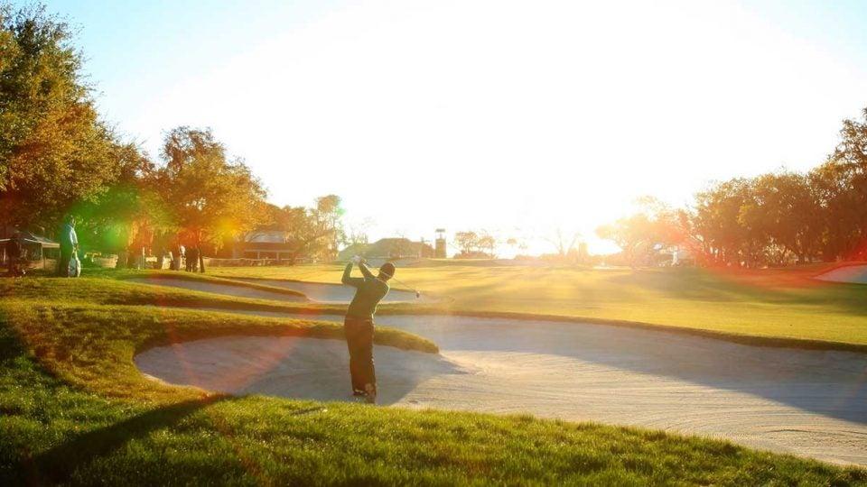 golfer splashes sand trap