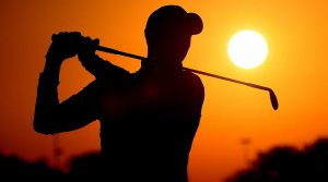 One golfer tee shot sunset