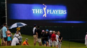 Spectators stand under video screen at Players Championship