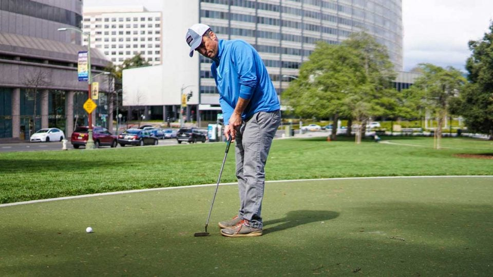 Golfer practices putting at Snow Park in Oakland, Calif.