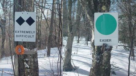 A black diamond and green circle sign at a ski slope.