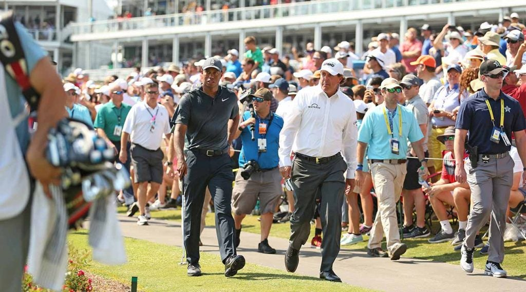 Tiger Woods and Phil Mickelson walk to the famed island green at TPC Sawgrass as hundreds of fans swarm.