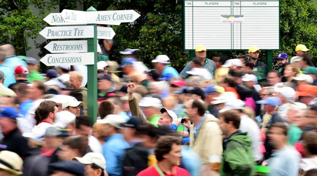 A sign pointing towards Amen Corner, awash in human activity.